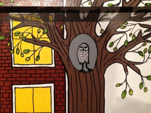 Detail of small owl in tree on the downtown mall